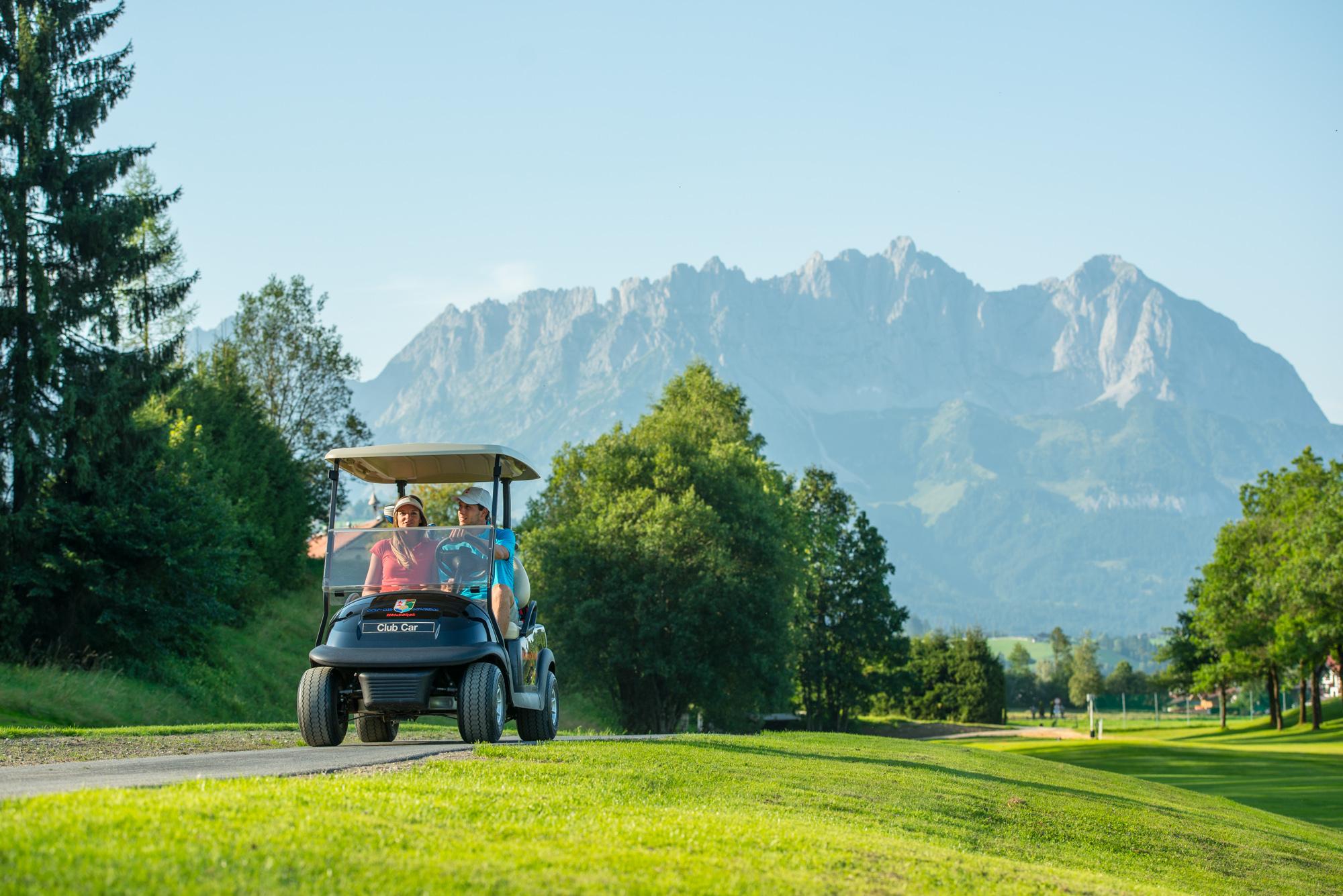 Paar im Golfcart auf dem Golfplatz in Kitzbühel