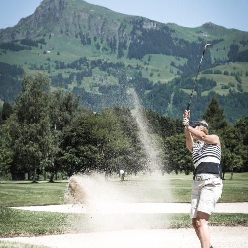 Golferin schlägt den Ball in Kitzbühel