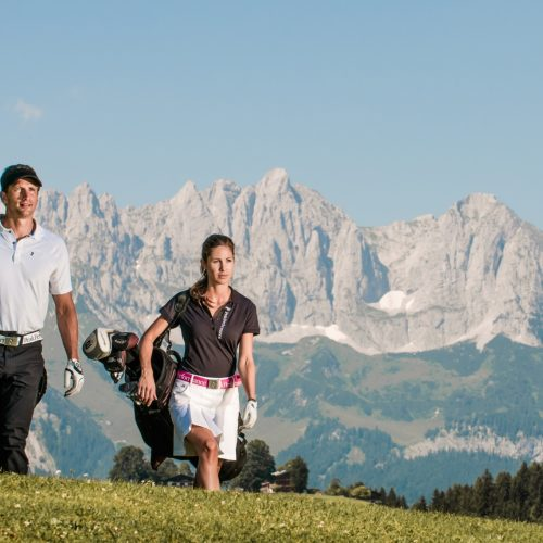 Paar in Golfausrüstung vor dem Hahnenkamm Alpen Kitzbühel