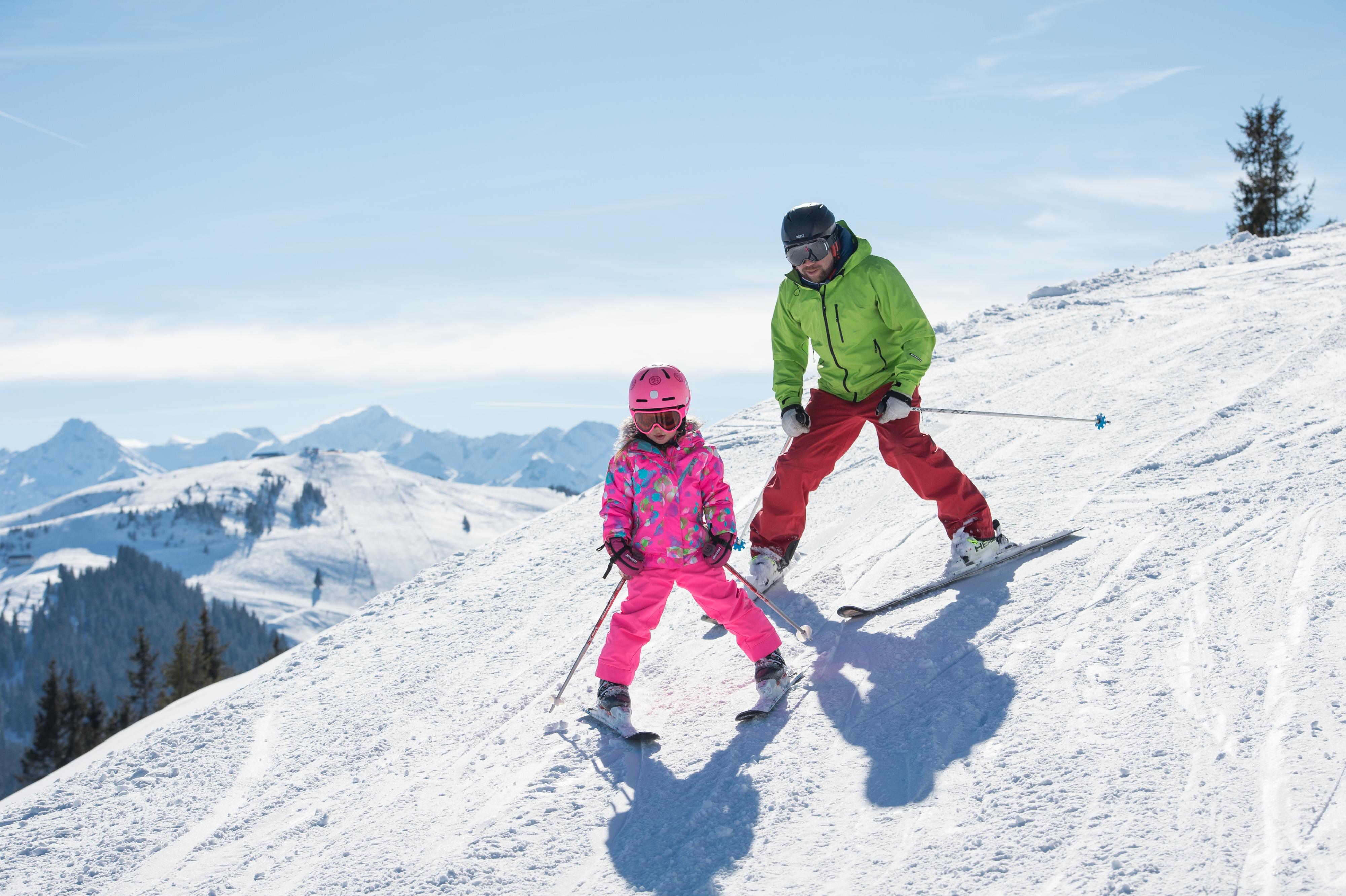 Vater und Tochter üben Skifahren in Kitzbühel