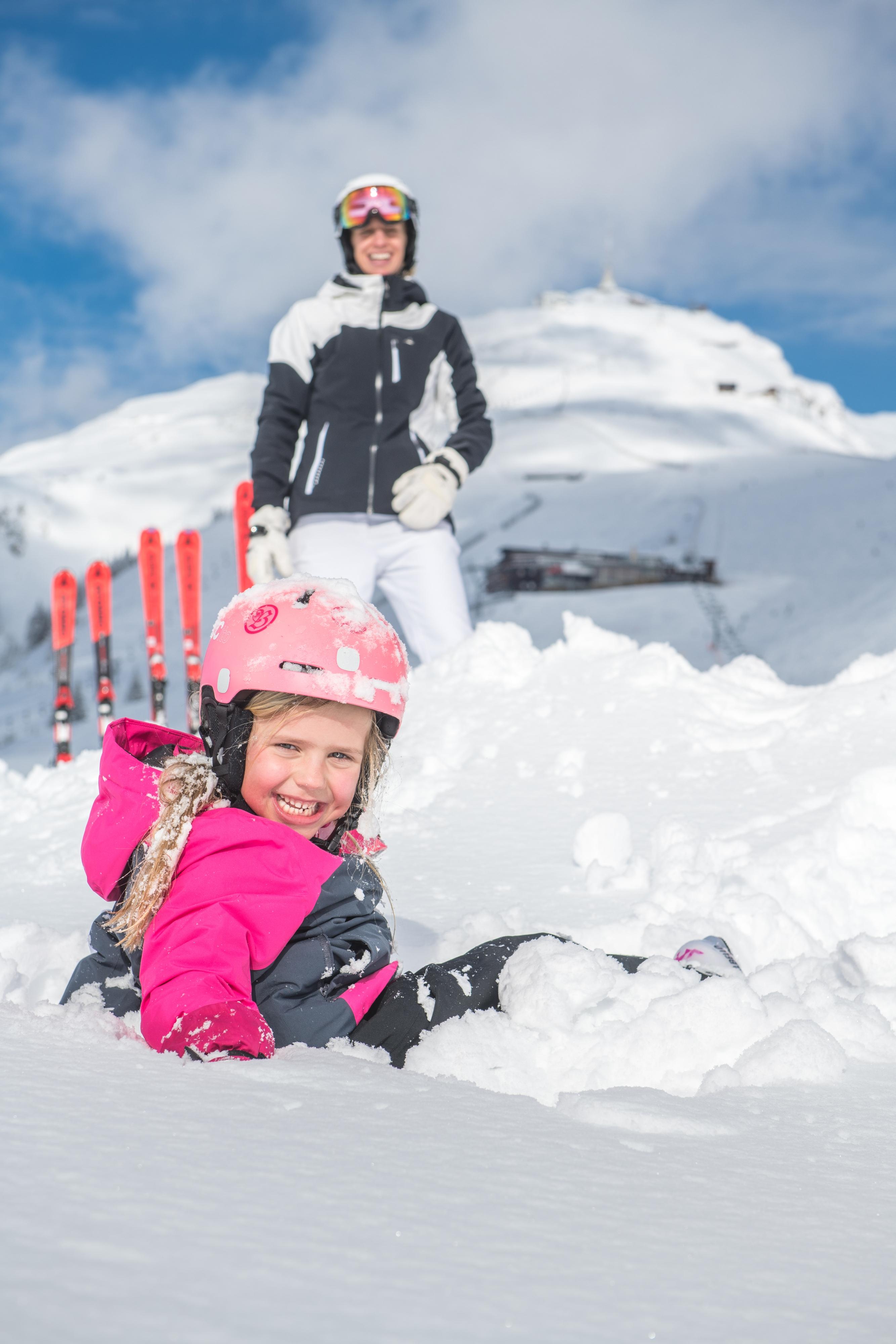 Mutter skifahren Kind liegt im Schnee