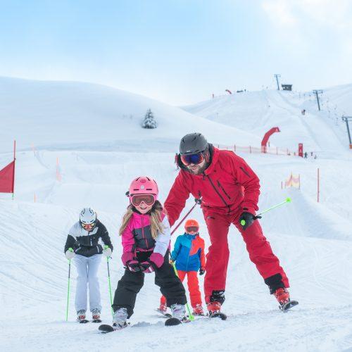 Eltern und Kinder üben Skifahren am Hahnenkamm Skigebiet in Kitzbühel