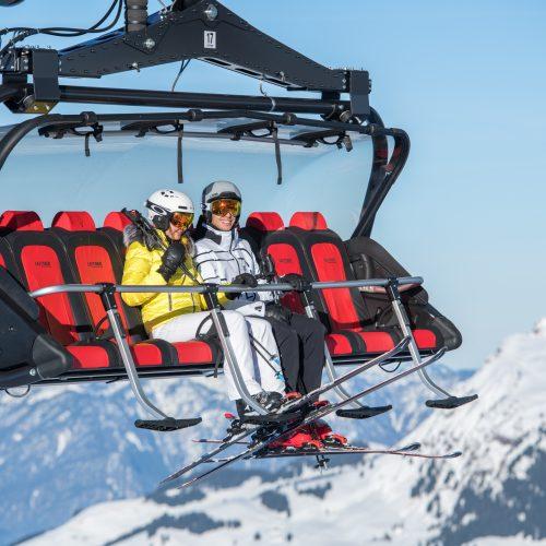 Paar sitzt im Skilift und fährt zum Skifahren in Kitzbühel