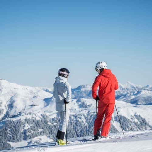 Frau und Mann fahren Ski und genießen die Aussicht Hahnenkamm in Kitzbühel