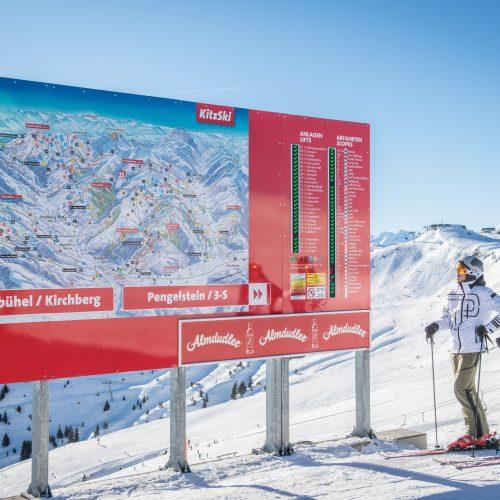 Paar betrachtet Tafel vom Skigebiet KitzSki