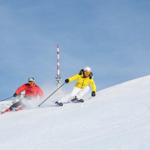Mann und Frau fahren schnell im Schnee Ski