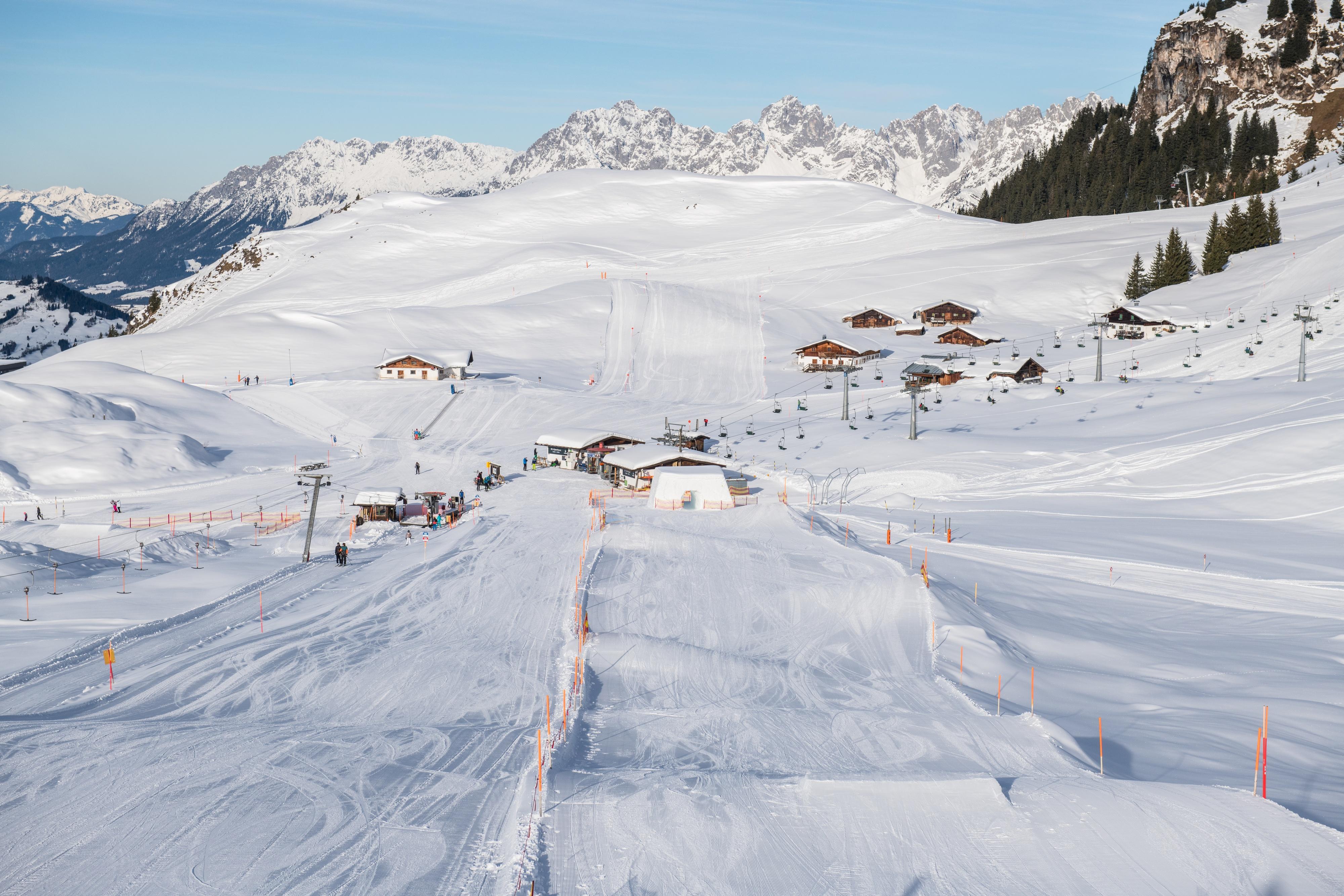 Piste Kitzbüheler Horn mit Bergen Alpen im Hintergrund und Hütten