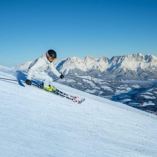 Frau fährt Ski steil bergab mit Blick auf Hahnenkamm
