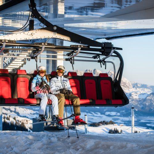 Frau und Mann im Skilift mit Hahnenkamm in Kitzbühel