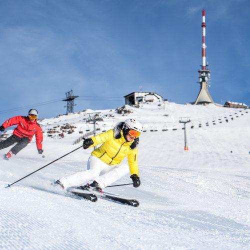 Mann und Frau fahren Ski Skigebiet KitzSki