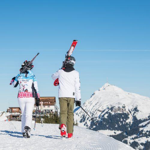Paar geht mit Skiern im Arm zur Hütte am Hahnenkamm