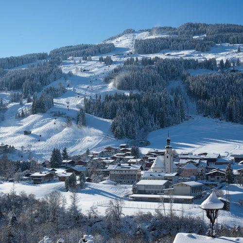 Stadt Jochberg bei Kitzbühel im Schnee umgeben von Bergen Skilift