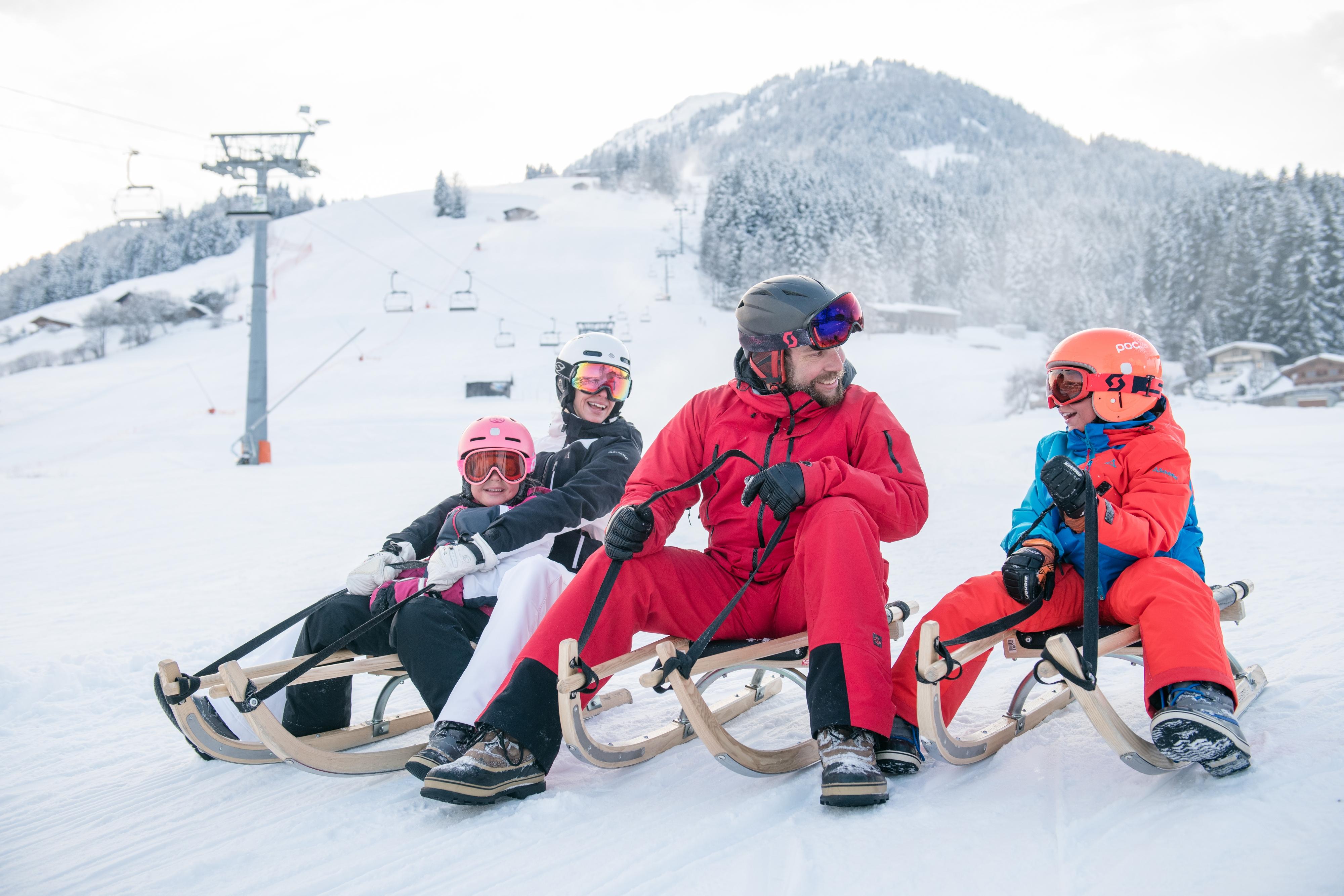 Rodeln mit Familie und Kinder Mädchen Junge Schlittenfahren