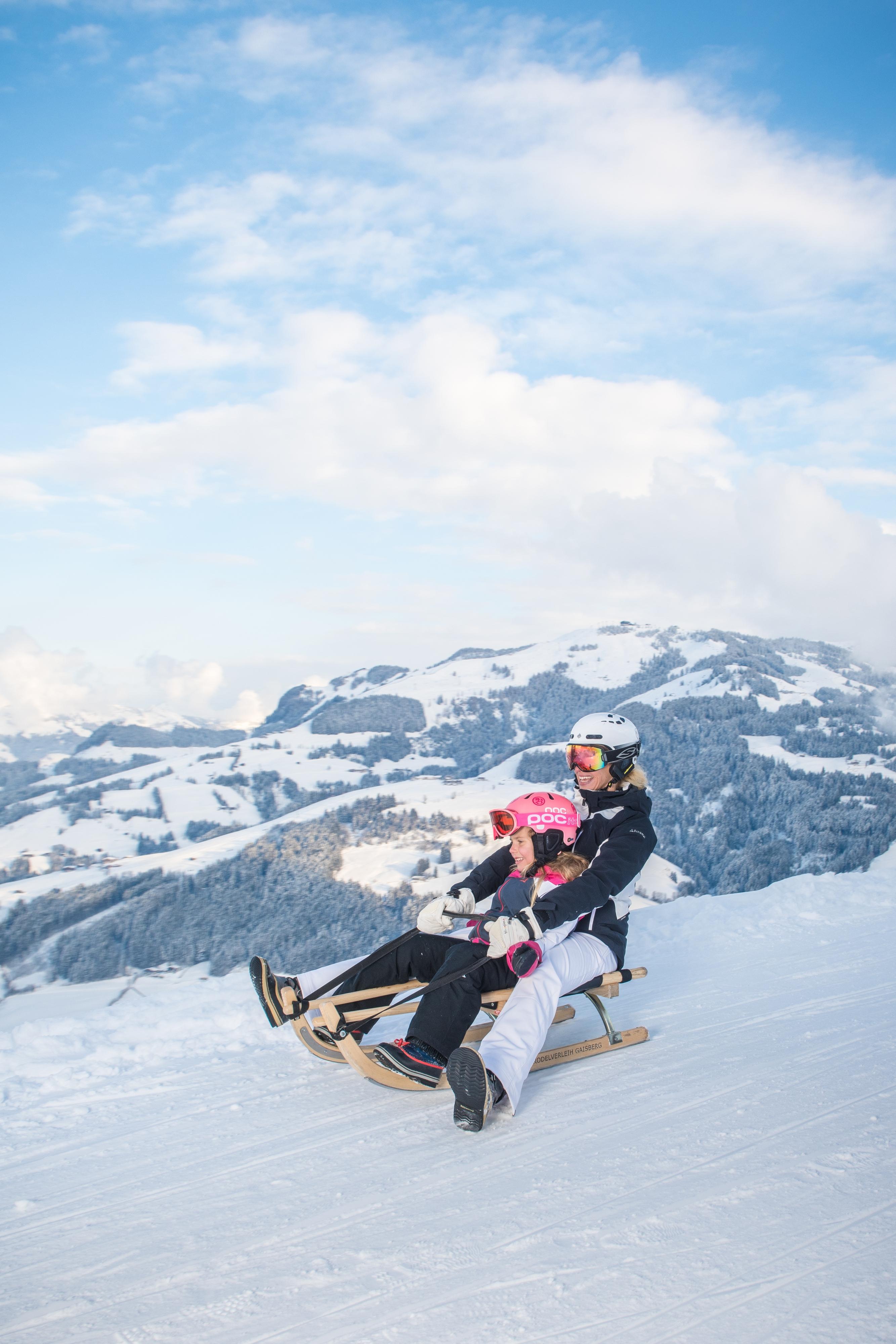 Frau Mutter mit Kind Tochter Mädchen Rodeln am Gaisberg in Kitzbühel