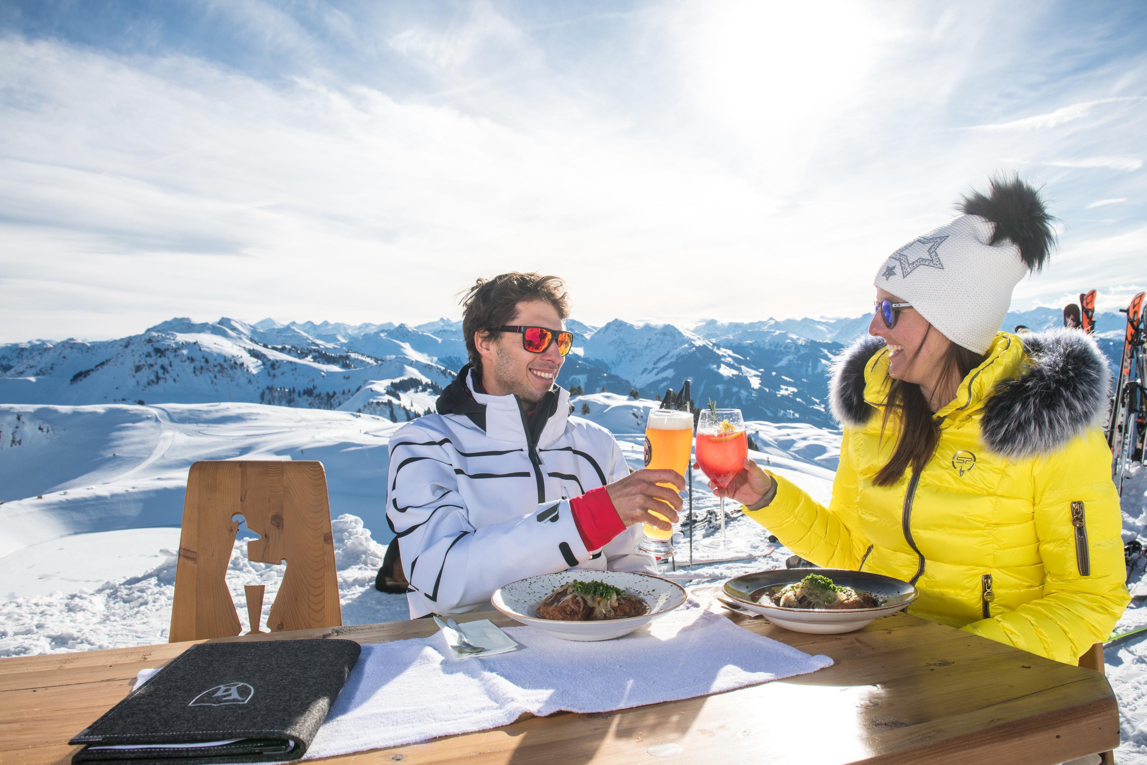 Einkehr Mann und Frau Mittagessen anstoßen mit Cocktail und Bier in Kitzbühel Skihütte Winter