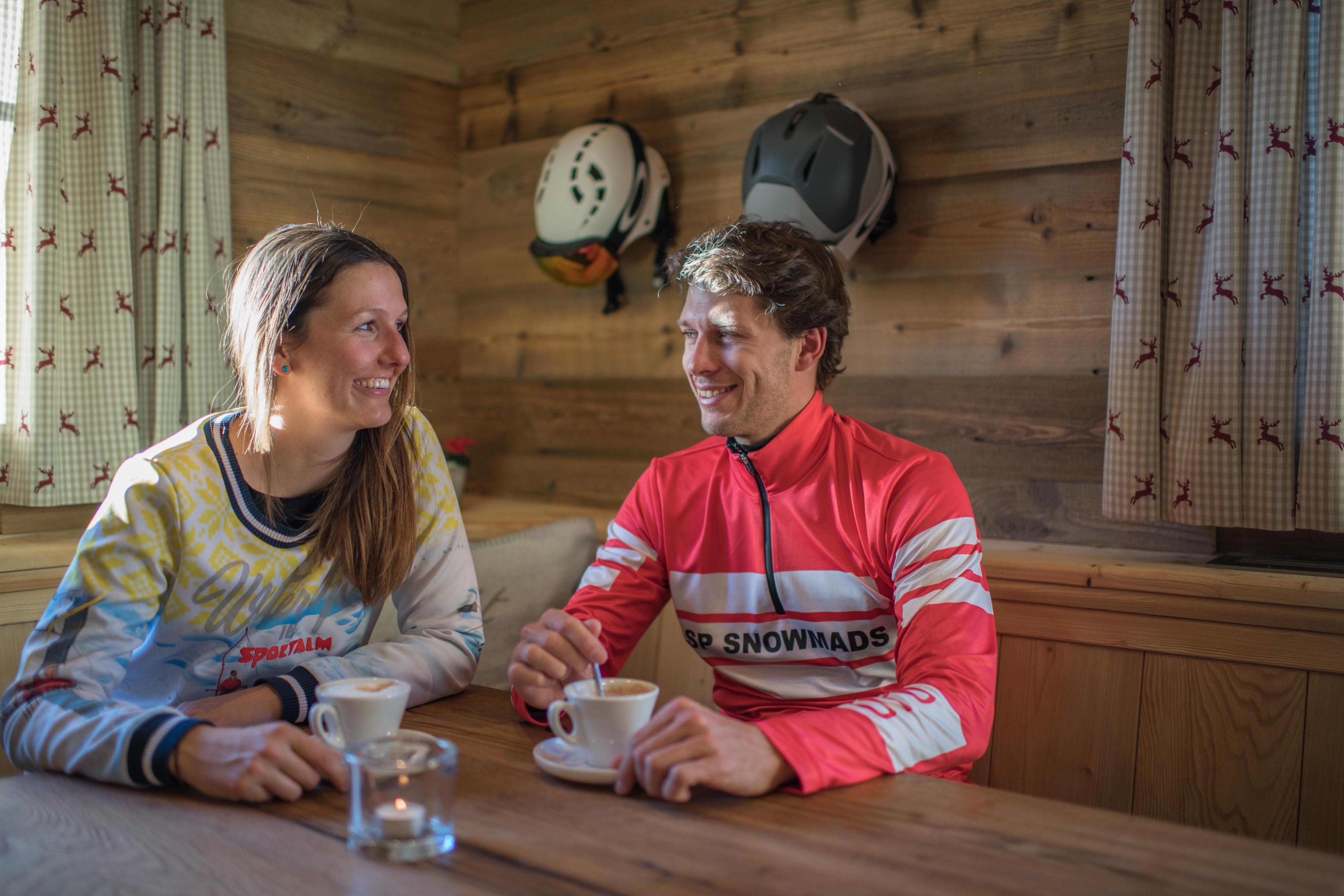 Mann und Frau nach dem Skifahren aufwärmen in Hütte mit Cappuccino