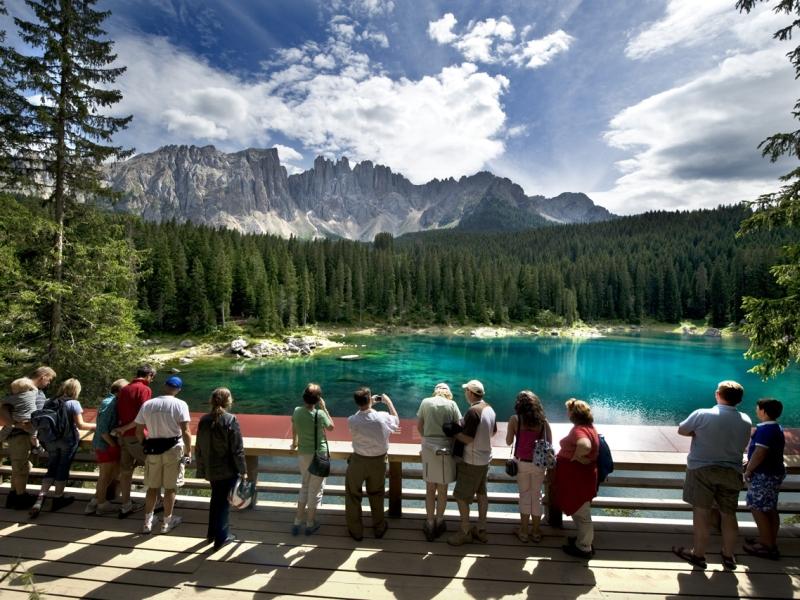 Besucher vor dem türkisen Karersee und Alpenpanorama