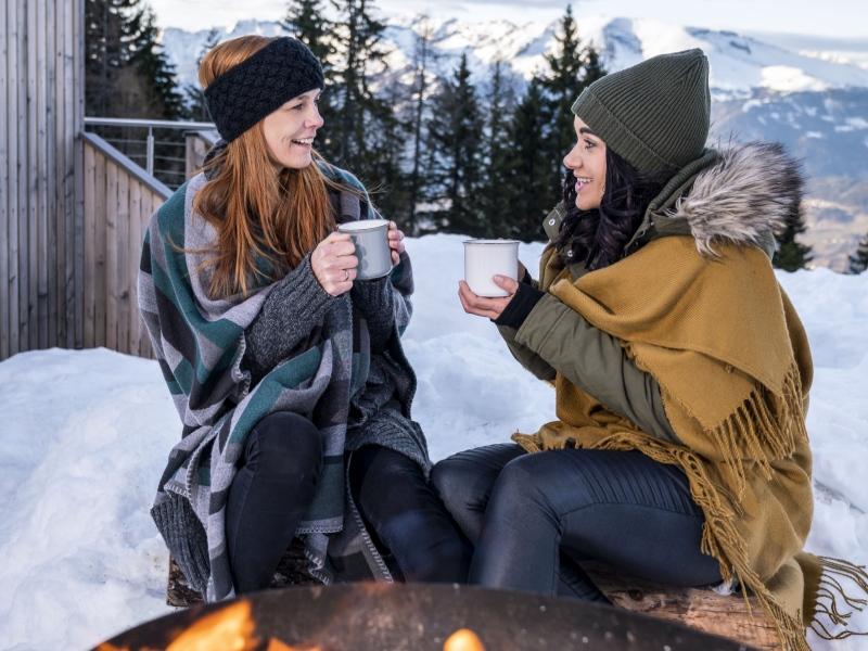Freundinnen unter Decken am Feuer mit heißen Getränken am Millstätter See