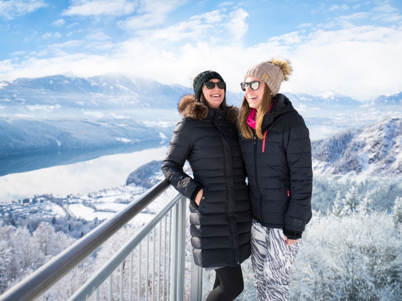 Freundinnen am Sternenbalkon mit Ausblick über den winterlichen Millstätter See