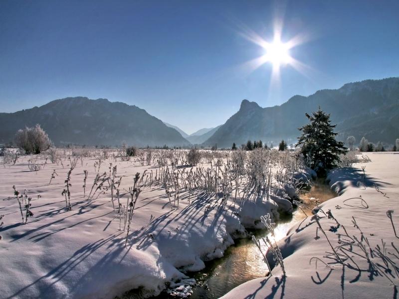 verschneites Moosgebiet mit Bach Berge im Hintergrund Sonnenschein