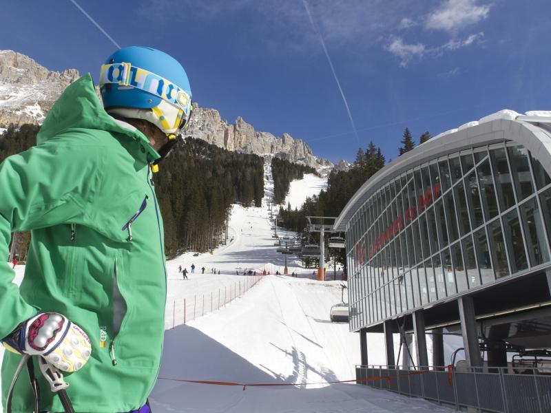 Skifahrer vor Sessellist Talstation Latemar