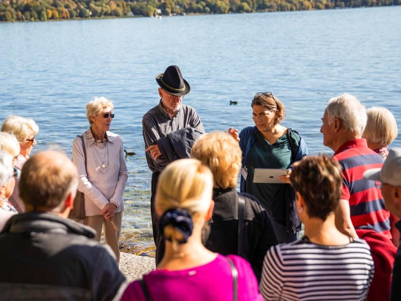 Menschengruppe im Gespräch am Ufer des Sees
