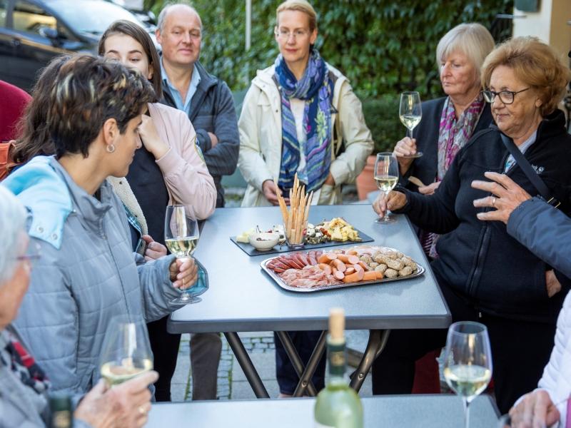 mehrere Personen am Stehtisch mit Wein und Schmankerl