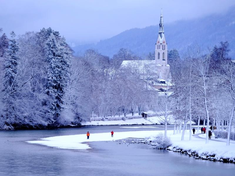 Winter Isar Spaziergänger Kirche im Hintergrund