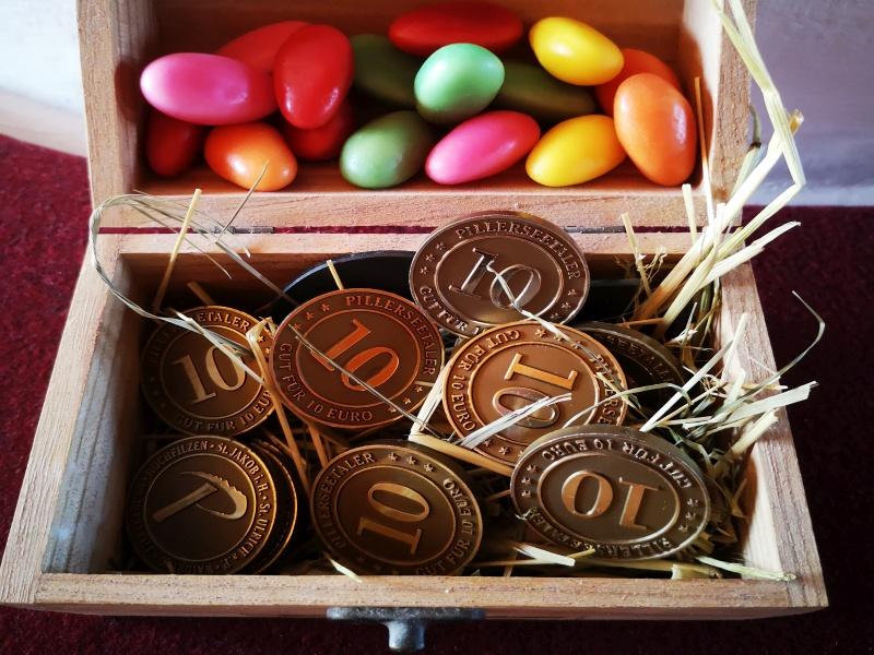 Holzkiste mit bunten Eiern und Pillerseetalern