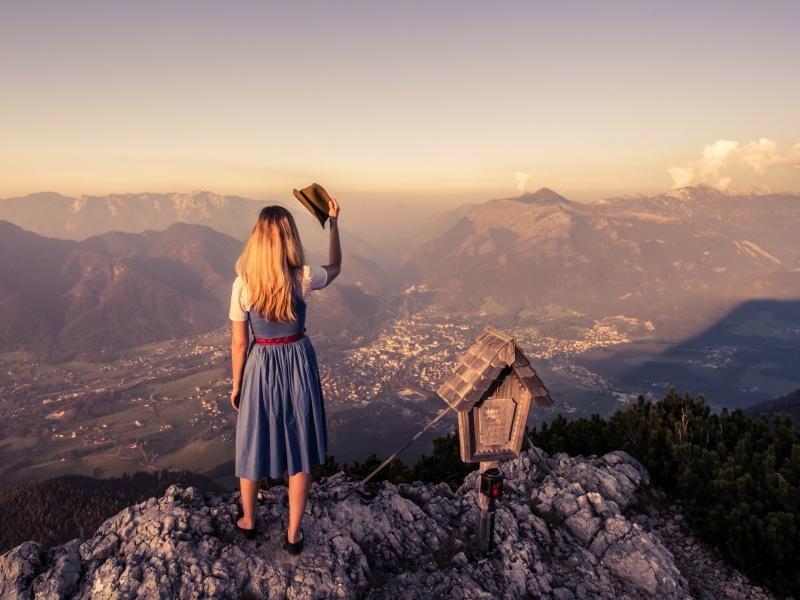 Frau im Dirndl auf Gipfel Blick ins Tal