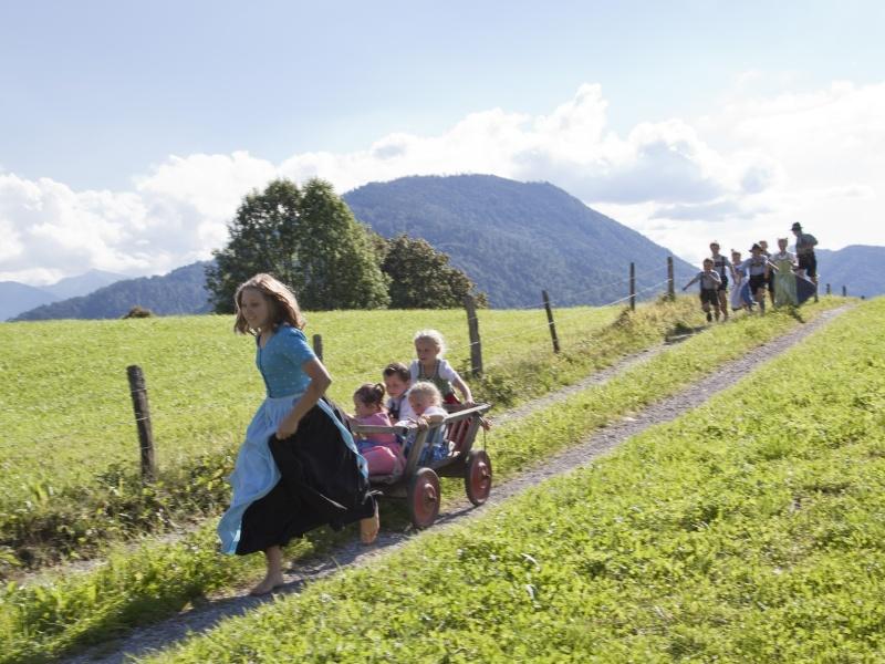 Kinder mit Bollerwagen auf Feldweg