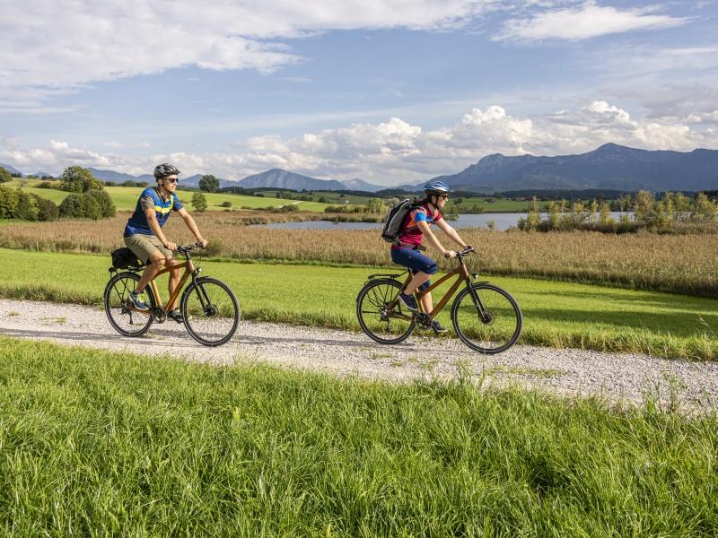 Radweg See im Hintergrund 2 Radfahrer