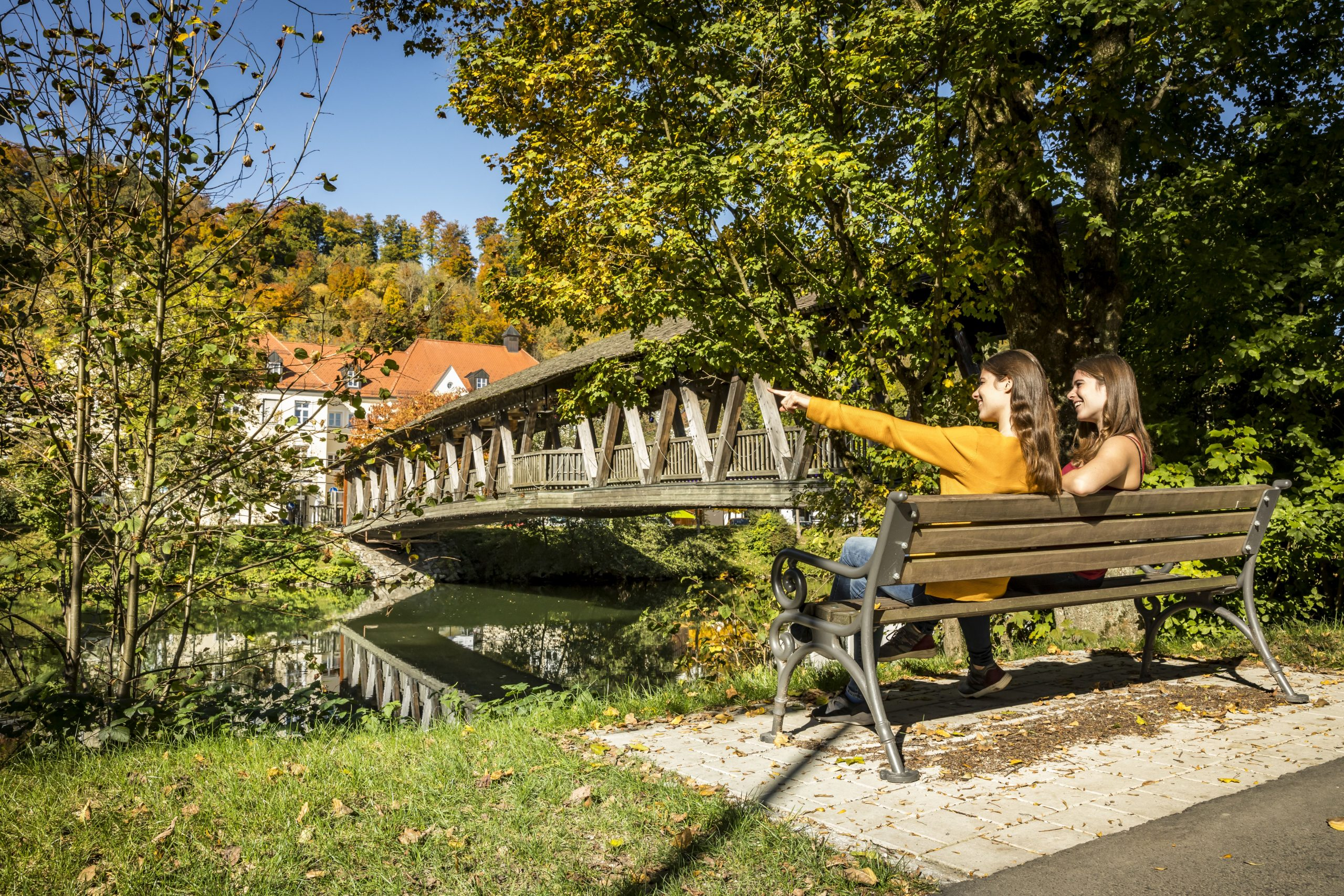 Holzbrücke über Fluss und zwei Personen