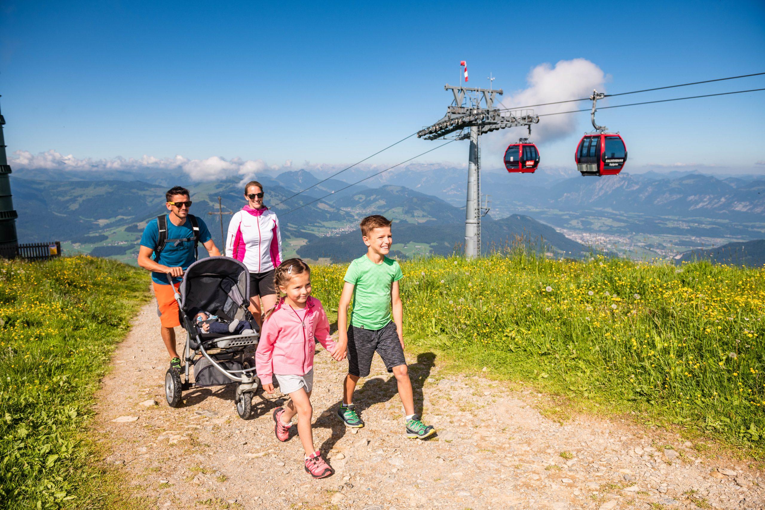 Familie spaziert auf Berg, dahinter Bergbahn