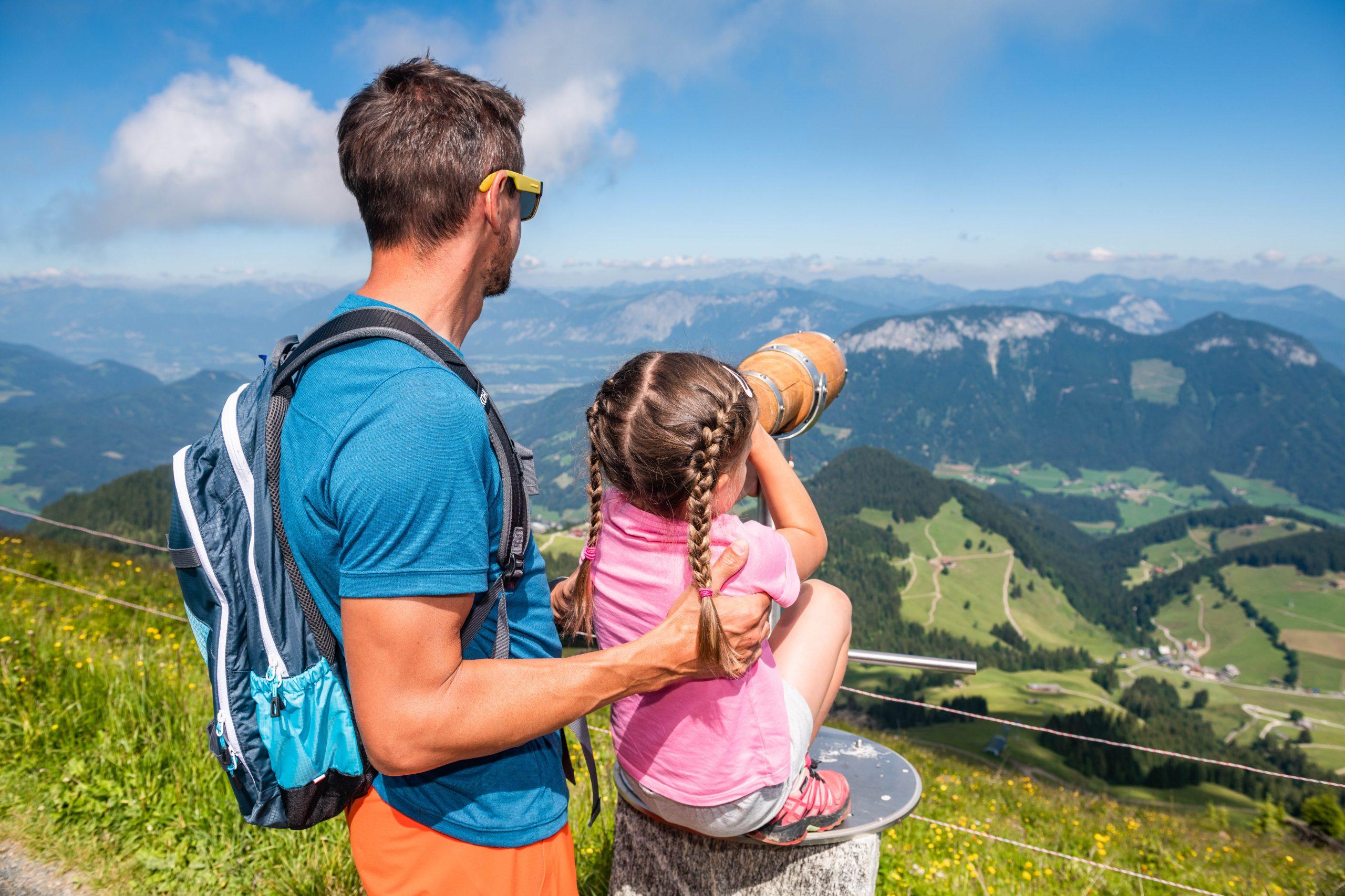 Vater mit Tochter auf Berg mit Fernrohr