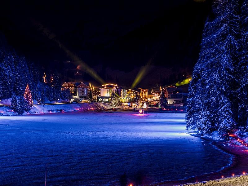 Bergsee im Winter mit bunter Beleuchtung