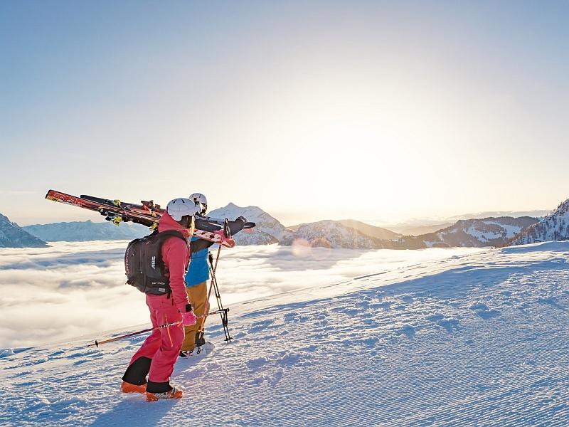 Skifahrer tragen Ski auf der Schulter