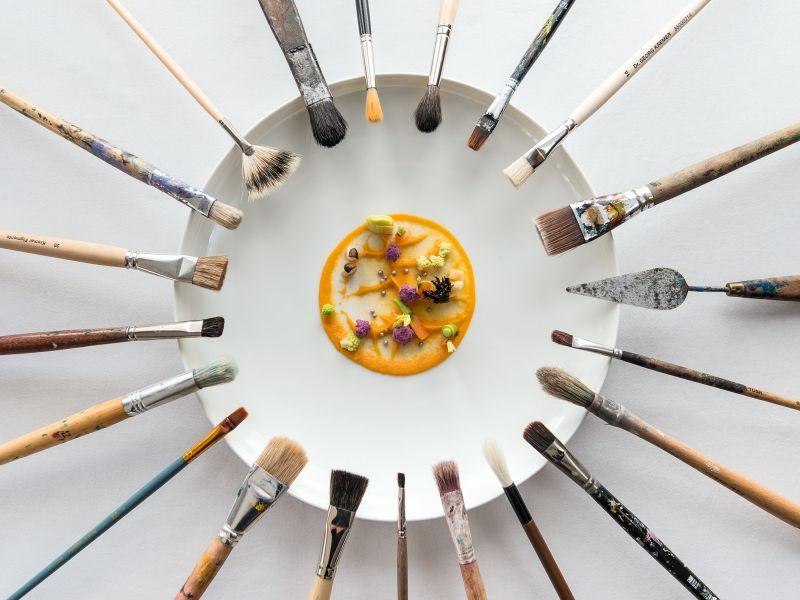 Kunstteller Speise mit vielen Pinseln am Tellerrand