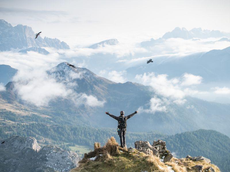 Person mit ausgebreiteten Armen auf Bergspitze